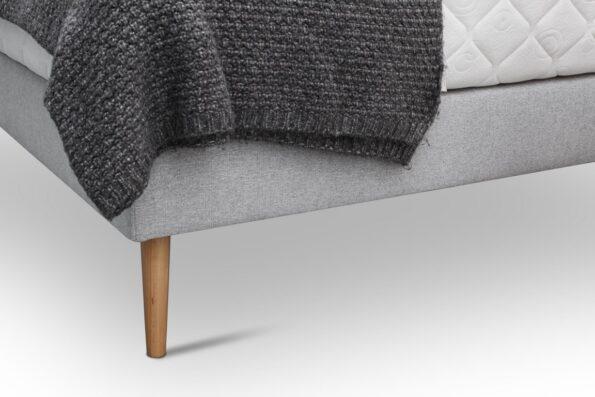 Łóżko tapicerowane na drewnianych nóżkach